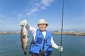stock photo of grouper  - happy asian senior fisherman showing large grouper fish - JPG
