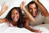 Couple Relaxing In Bed Hiding Under Duvet