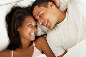 stock photo of snuggle  - Couple Relaxing In Bed Wearing Pajamas - JPG