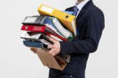 stock photo of fatigue  - Young business man carrying a bunch of folders - JPG