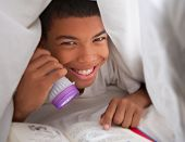 Boy Reading Book With Torch Under Duvet
