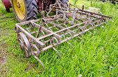 Tractor On Farm Field Gras With Metal Harrow