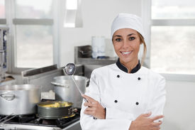 picture of kitchen utensils  - portrait of female chef looking at camera in kitchen - JPG