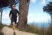 stock photo of crossed legs  - ocean trail running man doing daily fitness routine - JPG