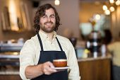 Portrait of confident waiter holding coffee cup while standing in cafe