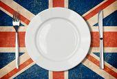 Plate, fork and knife on grunge UK flag