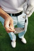 golfer removes dirt and sand from grooves of iron club with a tee peg