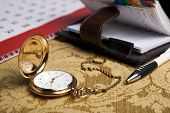 Gold Pocket Watch And A Wall Calendar And Sketchpad