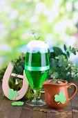 Glass of green beer, pitcher with coins and horseshoe on natural background close-up