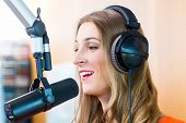 Female presenter or host in radio station hosting show for radio live in Studio