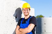 Pride builder standing on construction or building site with sewage or canalization concrete element