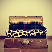 picture of a pile of warming blankets in an old suitcase, with a retro effect