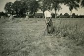 GERMANY, CIRCA 1940: Vintage portrait of farmer working with scythe