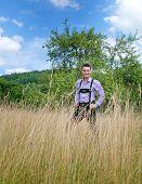 picture of lederhosen  - Young man in traditional Bavarian lederhosen walking alone in the field - JPG
