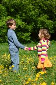 Boy And  Girl Handshaking Among Blossoming Dandelions