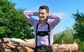 picture of lederhosen  - Young man wearing traditional Bavarian lederhosen posing in countryside - JPG