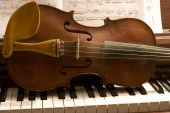 Old violin lying on a piano keyboard with sheet music behind