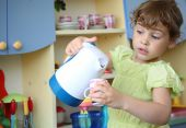 stock photo of young girls  - little girl with kettle and cup in hands - JPG