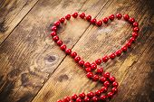 Heart Shape Pearl Necklace, A Wooden Background.