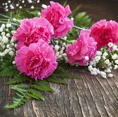 image of carnations  - Bouquet of Pink Carnation On Wooden Background - JPG