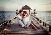 picture of caress  - Happy loving couple in white clothes posing on a pier on Maldives - JPG