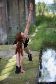 Pretty fit woman exercising in black gymnastic outfit in postindustrial environment