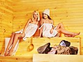 Women pouring water on rock in sauna.