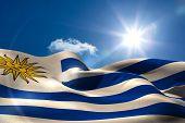 Digitally generated uruguay flag rippling against blue sky