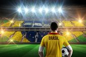 Brasil football player holding ball against stadium full of brasil football fans