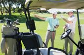 stock photo of buggy  - Golfing friends standing beside their buggy looking around on a sunny day at the golf course - JPG