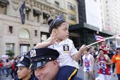 Little girl in NYPD uniform riding on dad's shoulders