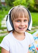 Portrait of cute 5 years girl wearing wireless headphones outdoors