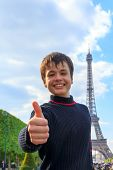 Cheerful Teenager Shows Thumb Up Near Eiffel Tower (la Tour Eiffel)