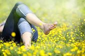 stock photo of sunbather  - Relaxing in a meadow full of buttercups in the summer sun - JPG