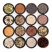 Seed super food selection in wooden bowls over white background.