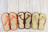 High angle shot of a group of summer beach sandals on a wooden deck. The mulit-colored sandals are lined up in a row by pair.