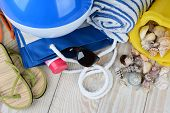 A group of items for a day at the beach, sandals, beach ball, tote bag, sunglasses, towel and sand pail with sea shells, and sun tan lotion. Horizontal format on a wooden deck.