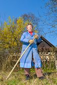 stock photo of hoe  - Elderly woman in blue coat posing in front of a house with hoe in her hands - JPG