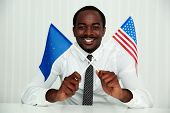 African businessman sitting at the table and holding USA and European flags