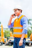 Asian foreman telephoning with mobile phone of building site or mining or rental company