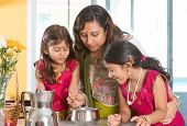 Asian family cooking food together at home. Indian mother and children preparing meal in kitchen. Tr