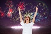 Cheering football fan in white against fireworks exploding over football stadium