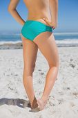 Lower half of fit woman standing on beach on a sunny day