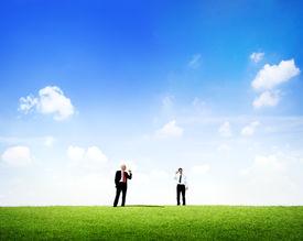 foto of tin man  - Two business men standing in outdoors talking through tin can phone - JPG