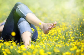 stock photo of buttercup  - Relaxing in a meadow full of buttercups in the summer sun - JPG