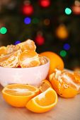 stock photo of tangerine-tree  - Sweet tangerines and oranges on table on Christmas tree background - JPG