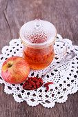 Goji berries drink in glass cup, ripe apple and raisins in metal spoon on lace napkin on wooden background