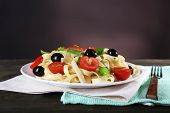 Spaghetti with tomatoes, olives and basil leaves on plate on napkin on table on wall background