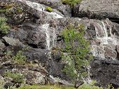 Northern travel, waterfall in the mountains, amid the stones.