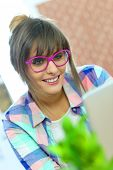 Young woman with pink eyeglasses websurfing with tablet